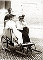 Two women in a tandem roller chair wheeled by an uniformed African-American man at the 1904 World's Fair.jpg
