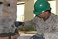 U.S. Marine Corps Lance Cpl. Christopher A. Cornelison, with the 9th Engineer Support Battalion, 3rd Marine Logistics Group, III Marine Expeditionary Force, lays brick in a door frame during renovation work on 130725-M-DR618-049.jpg
