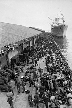 Troops unload supplies from a boat at a pier