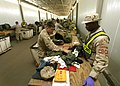 US Navy 051229-N-3607D-001 Aviation Structural Mechanic 2nd Class Christopher Hunter, assigned to Navy Customs Battalion Papa, prepares to inspect a soldier's personal belongings.jpg