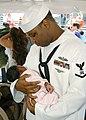 US Navy 060524-N-6433N-027 Storekeeper 3rd Class Larry Jones holds his baby for the first time after returning to Norfolk aboard the Nimitz-class aircraft carrier USS George Washington (CVN 73).jpg