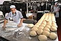 US Navy 060602-N-1332Y-025 Culinary Specialist Seaman D'arco Tolliver assigned aboard the USS Kitty Hawk (CV 63), rolls pizza dough in preparation of a celebration for 273 recently promoted Sailors.jpg
