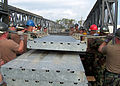 US Navy 070405-N-2374M-034 Seabees assigned to Naval Mobile Construction Battalion (NMCB) 24, and Naval Mobile Construction Battalion (NMCB) 27 lift a component of a Medium Girder Bridge into place during a bridge building clas.jpg