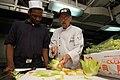 US Navy 071022-N-5387K-007 Chef Ray Duey instructs Culinary Specialist Seaman Keyon Burrell on how to make a vegetable garnish aboard USS Kitty Hawk (CV 63).jpg