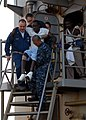 US Navy 100124-N-4971L-028 Sailors aboard USS Fort McHenry (LSD 43) carry injured Haitian medical evacuees to an MH-60S Sea Hawk helicopter.jpg