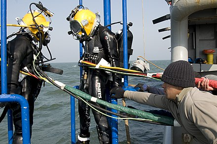 A South Korean and U.S. diver during the recovery phase US Navy 100409-N-9123L-002 Dive tenders recover divers aboard the Military Sealift Command rescue and salvage ship USNS Salvor (T-ARS 52).jpg