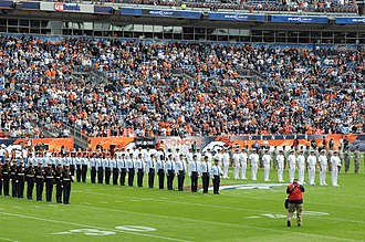 United States Armed Forces - Service members of the U.S. Armed Forces at an American football event: (left to right) U.S. Marine Corps, U.S. Air Force, U.S. Navy and U.S. Army personnel