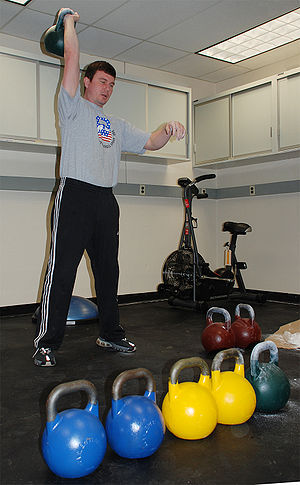 Kettlebell lifting - Valery Fedorenko demonstrates a basic snatch manoeuvre. Red (32 kg), green (24 kg), yellow (16 kg), and blue (12 kg) standard kettlebells are seen.