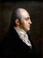 A man with receding gray hair tied in a braid, wearing a high-collared white shirt and black jacket