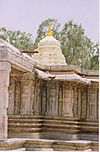 View of wall relief with sikhara in background at Vaidyeshvara temple at Talakad.jpg