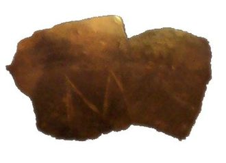"""Vinča symbols - Fragment of a clay vessel with an """"M""""-looking incision."""