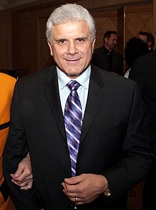 An Italian-Canadian man in his sixties with grey hair, wearing a tuxedo with a light blue shirt and purple tie, facing the camera.