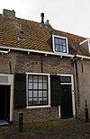 foto van Eenvoudig woonhuis in gele baksteen onder een gezamenlijk dwars met pannen belegd zadeldak met de nrs 6,8 en 10