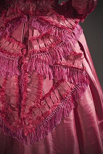 Trim (sewing) - Red fringe trim on a woman's dress c. 1870.