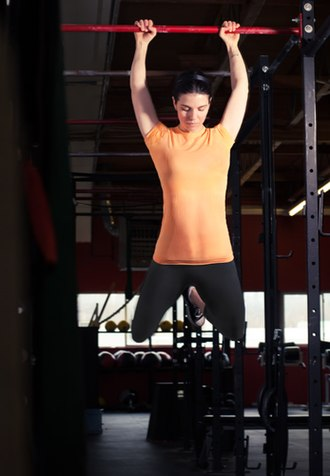 CrossFit - A woman doing a kipping pull-up