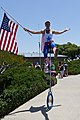 Young man on unicycle with American flag. People at Morro Bay, CA Fourth of July 2011 Celebration (5902689881).jpg