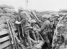 Several members of the 1/7KR in a deep trench. In the foreground, another member stands on a firing step in order to peer over the parapet composed of sandbags.