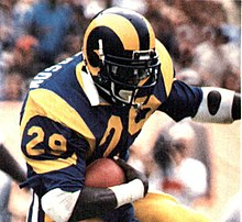 Eric Dickerson running with the ball in a football game.