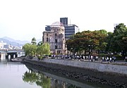 Citizens of Hiroshima walk by the Hiroshima Peace Memorial, the closest building to have survived the city's atomic bombing.