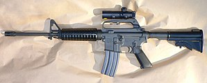 Assault weapon - The Colt AR-15 Carbine is a semi-automatic rifle that fires one round each time the trigger is pulled, featuring a pistol grip, telescopic stock, and flash suppressor.