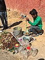 A boy selling honey by squeezing it from the honeycomb by hands alongside a road in Bengaluru, India.jpg