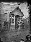 A man, child and woman standing outside a shop NLW3365044.jpg