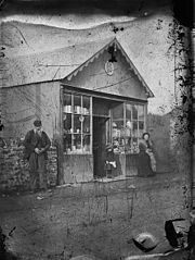 A man, child and woman standing outside a shop
