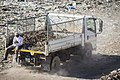 A man rides on a dump truck.jpg