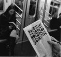 A person works on a crossword puzzle in the subway 2008.tif