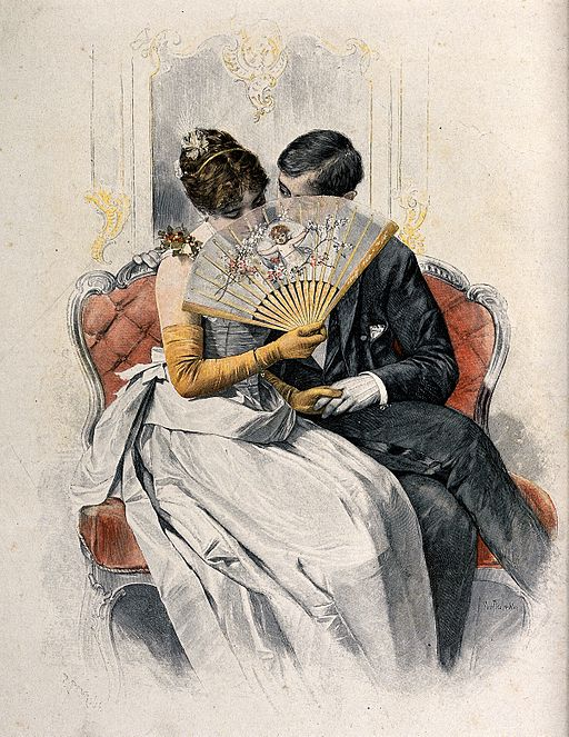 A young couple sit on a sofa holding hands while she coyly Wellcome V0039049