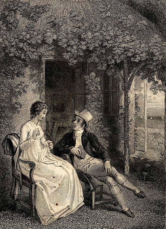 A young couple sit talking in a garden.