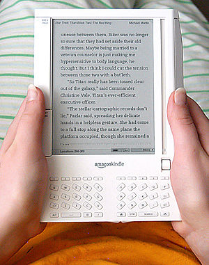 Amazon Kindle e-book reader being held by my g...
