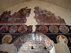 A partially preserved fresco of a biblical scene with portraits of Christian figures in circles below, all painted above a portal