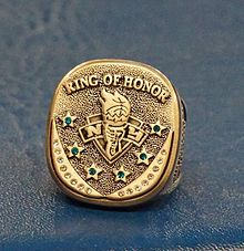 "A gold ring with the words quote ring of honor"" at the top six stars with jewelsin the symbol of the New York Liberty in the center"