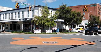 Auburn University traditions - Tiger Paw painted on the street at Toomer's Corner with Toomer's Drugs in the background.