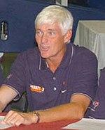 Um homem caucasiano mais velho, tan de cabelos brancos está sentado em uma cadeira atrás de uma mesa, enquanto falando com alguém fora da câmera.  Ele está vestindo uma camisa de manga curta azul escuro pólo e um ouro e relógio de prata em seu pulso esquerdo.