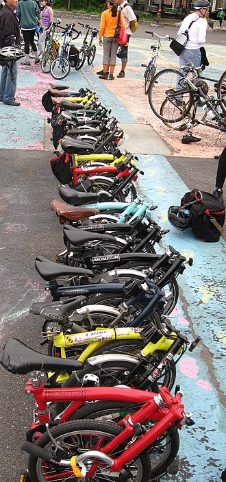 Brompton Bicycle - Different colour folded Brompton Bicycles in New York. Half retain their supplied stock saddle