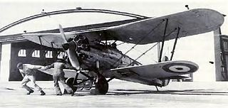 Two men swinging the propeller of a biplane in front of a hangar