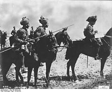 Three Indian horsemen in the foreground, the man on the left carries a lance a sergeant is in the middle and an officer on the right. In the background can be seen three further cavalrymen
