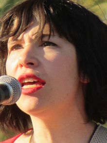 Closeup image of Brownstein singing into a microphone