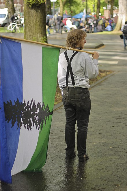 Person in Portland, Oregon with Cascadian Flag on International Worker's Day, 2012 Cascadia Flag (7134901861).jpg