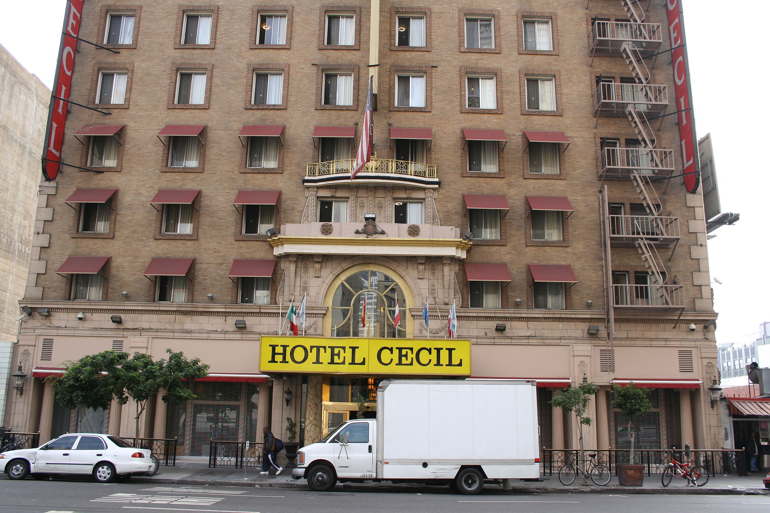 """黄褐色の煉瓦造りの建物。下階の部屋の窓には日除けがついている。右側には避難経路がある。通りに面した出入り口の上には、黄の背景に黒い文字で""""Hotel Cecil""""と書かれている。"""