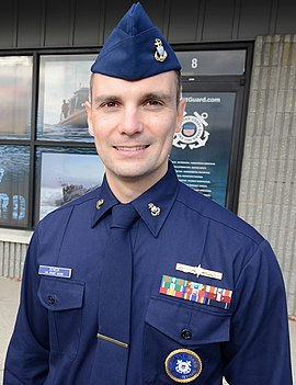 A U.S. Coast Guard recruiter wearing the Winter Dress Blue uniform with garrison cap Chief Petty Officer Nick Scheck stands in front of Coast Guard Recruiting Office Atlantic City, New Jersey.jpg