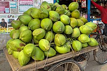 Stack of green coconuts on cart