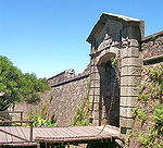 Stone wall with gate and draw bridge.