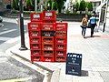 Crates of empty Coke bottles waiting on sidewalk for collection (18810884241).jpg