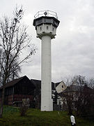 A tall white tower standing near houses and a barn; its base is formed by a slim round column, at the top of which is an octagonal cabin with top-hung windows facing into all directions; there is a searchlight on top of the tower's flat roof, and a railing around the roof's outer edge.
