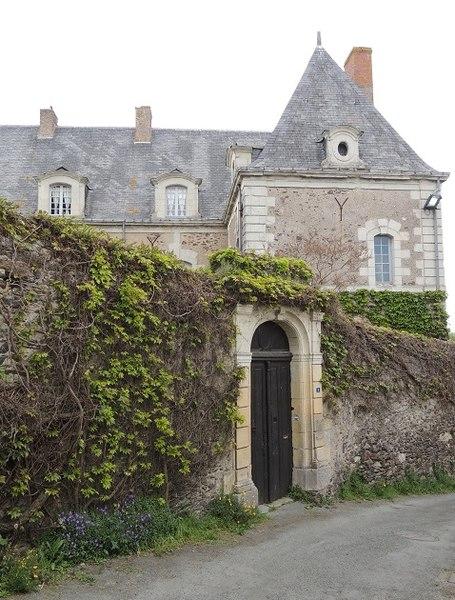 Presbytère: élévation et toiture du batiment principal au dessus du haut mur de cloture avec un beau portail en pierres de taille blanches derrière la route au 1er plan, mur couvert de lierre.