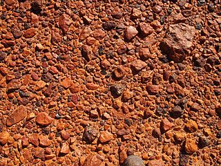 A desert surface covered with closely packed, interlocking angular or rounded rock fragments of pebble and cobble size.