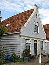 foto van Houten huis, gepotdekselde zijwanden en puntvormig voorschot. Goede pui en puilijst